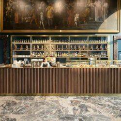Op maat gemaakte bar met houten gevel en metalen plinten voor een verfijnd restaurant