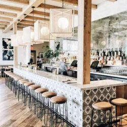 Designer barteller in stenen blad en onderstel met tegels en metalen voetrail voor een modern restaurant