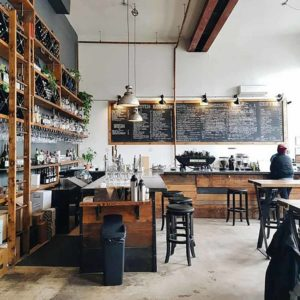 Brown Rustic Industrial Design Cafe Counter with Granite Counter Top and Wooden Plank Elevation