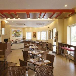 Ensembles de salle à manger de meubles en rotin et tabourets de bar avec tables hautes dans un espace buffet de l'hôtel